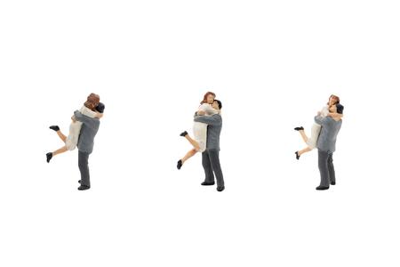 Miniature couple hugging isolated on white background