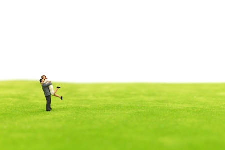 Miniature couple hugging on green fields in white background, valentine concept