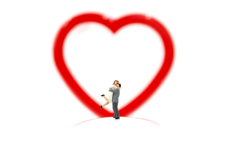 Miniature couple hugging and red heart on white background, valentine concept