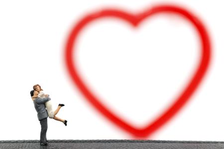 Miniature couple hugging on white background, valentine concept Stock Photo