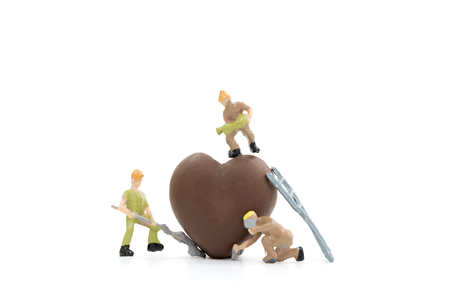 Miniature worker making heart shaped chocolate on white background , valentine concept.