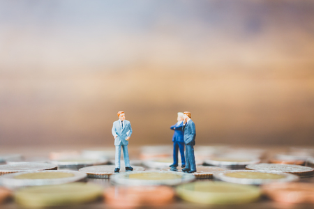 Miniature people businessman standing on money with  wooden background Stock Photo