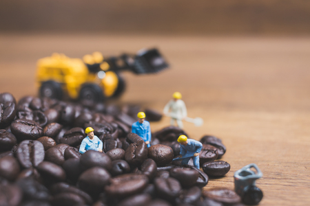 Miniature people working on roasted coffee beans