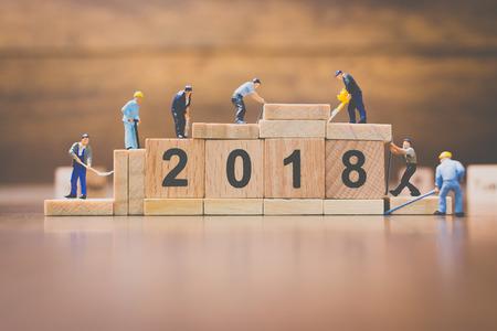 Miniatuurwerker teamgebouw houten bloknummer 2018 op houten achtergrond