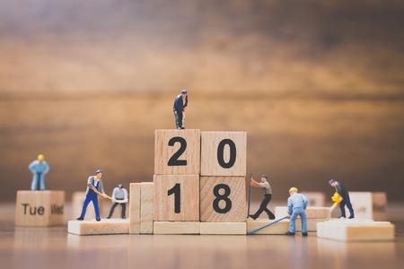 Miniature worker team building wooden block number 2018 on wooden background