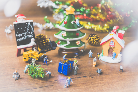 Creative concept with miniature people creating Christmas decorations on a wooden background. , Concept of teamwork.