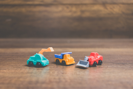 Toy construction machinery on wooden background Stock Photo