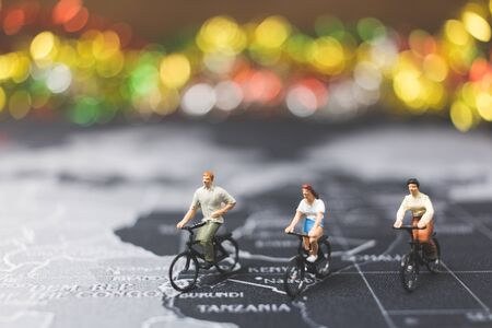 small world: Miniature people travelers riding bicycle on world map , Traveling and exploring the world Concept Stock Photo