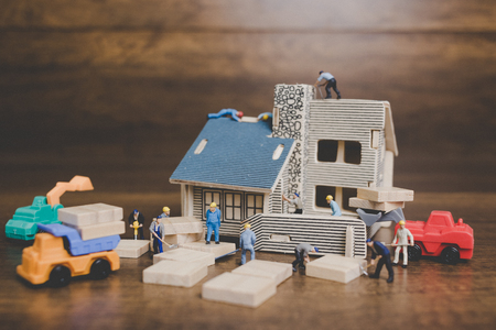 Miniature people worker repairing are repairing house on wooden background. Stock Photo