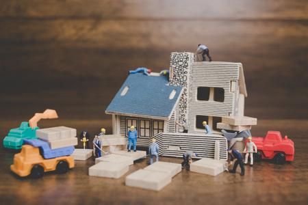 Miniature people worker repairing are repairing house on wooden background. Banco de Imagens