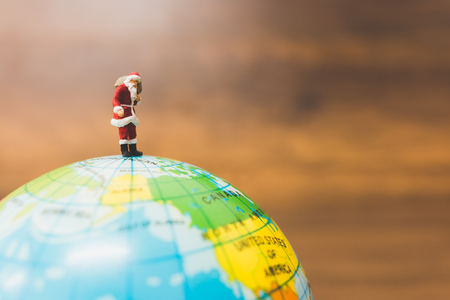 Miniature people : Santa Claus carrying on The globe