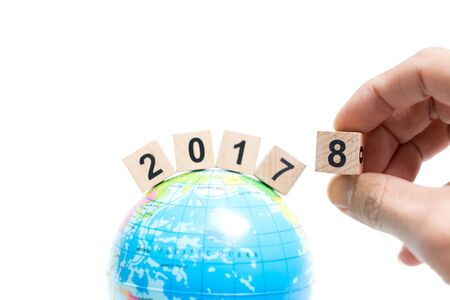 Hand holding Wooden block number 8 on globe map , New year concept