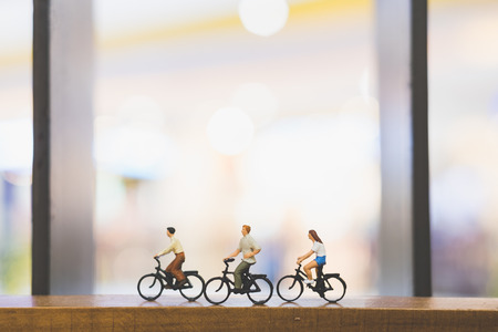 ミニチュアの人々:木製の橋の上に自転車を持つ旅行者 写真素材