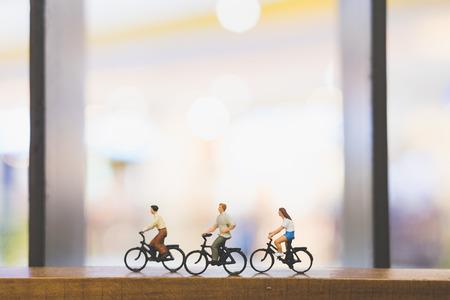 Miniatuurmensen: reizigers met fiets op houten brug