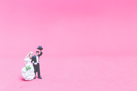 Miniature people wedding , Bride and groom on pink background , Valentine's day concept