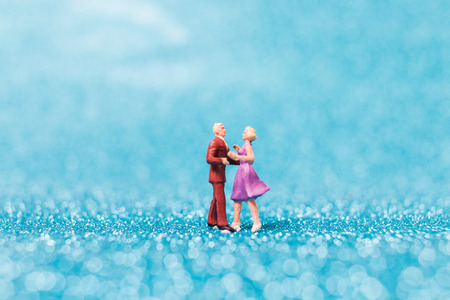 Miniature people , Couple dancing on blue glitter background , Valentines day concept