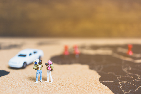 Miniature people travelers walking on world map , Traveling and exploring the world Concept Stock Photo