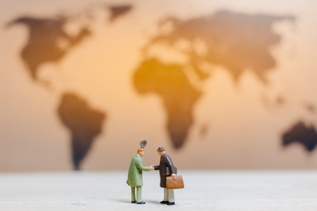 Miniature people :Businessman standing on world map Background , Growing business concept