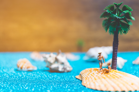 Miniature people wearing swimsuit relaxing on a seashell with blue glitter background