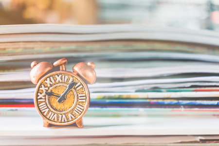 Ancient clock and stack of book with warm lighting background