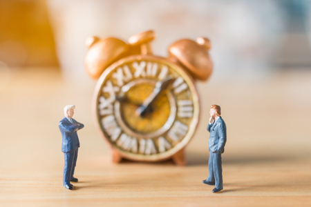 Miniature people: Businessman standing with Ancient clock on wooden background Stock Photo