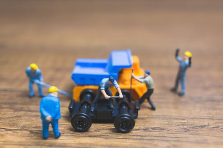 Miniature people : Worker repairing wheel of a truck on wooden background