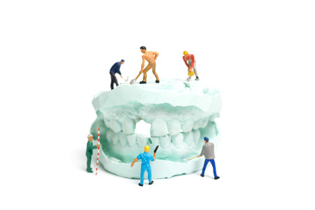 Miniature Worker team is filing fake teeth and placing them in a denture made with plaster. Dental prosthesis laboratory. Stock Photo