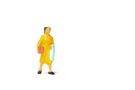 Miniature people : Traveler holding a handbag standing on white background , Travel concept