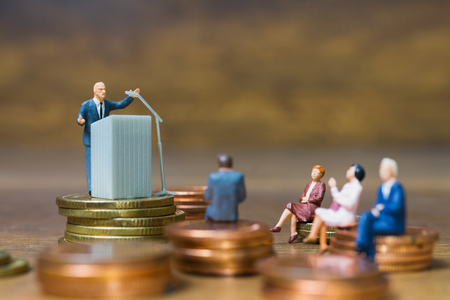 Miniature people : Businessman speaking on the podium , Business and finance investment concept Фото со стока