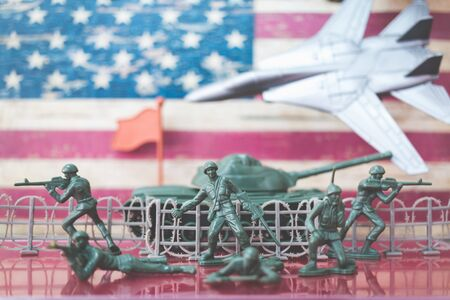 Miniature toy soldiers in battle scene with american flag background , Memorial Day concept