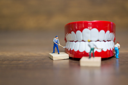 Miniature people : Worker team repairing a tooth ,Healthcare and medical concept