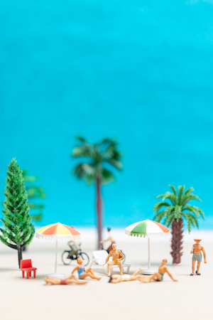 Miniature people wearing swimsuit relaxing on the beach  background