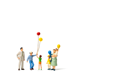 Miniature people : Happy family holding balloon on white background and copy space for text