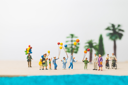 Miniature people : happy family enjoy summer vacation on the beach