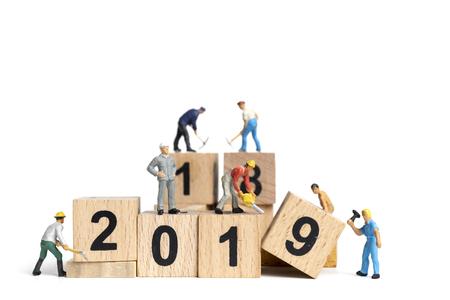 Miniaturarbeiterteam, das Nummer 2019 auf weißem Hintergrund malt, Frohes neues Jahr 2019 Konzept