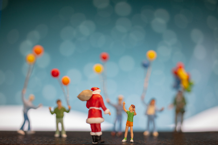 Miniature people: Santa Claus and children holding balloon , Merry Christmas and Happy New Year concept.