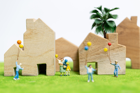 Miniature people : Happy family walking in field with balloons ,   Happy family relations and carefree leisure time Concept