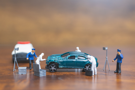 Miniature people : Police And Detective standing in front of car , Crime Scene Investigation concept