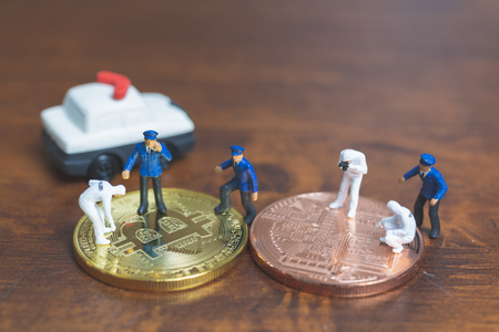 Miniature people : Police And Detective standing in front of Cryptocurrency bitcoin , Cyber crimes concept Stock Photo