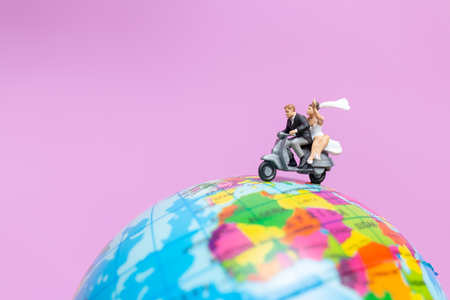 Miniature people : Couple riding the motorcycle on The Globe , Valentines concept