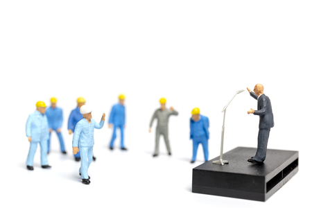Miniature people : A politician speaking to the people during an election rally Stock Photo