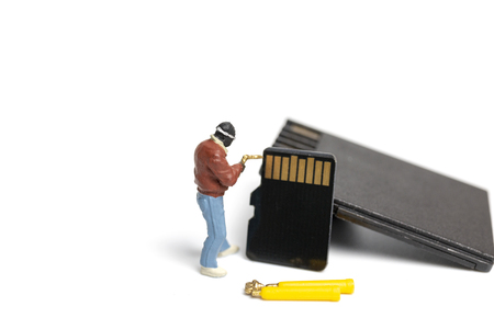 Miniature people technician fixing pile of sd cards on white background with copy space. Stock Photo