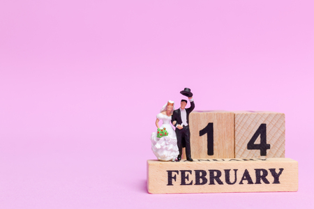 Miniature people wedding , bride and groom couple on pink  background , Valentines Day concept