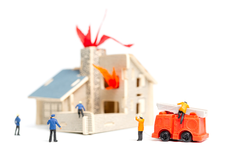 Miniature people : Firefighters with water pistols are taking care of a fire emergency Stock Photo