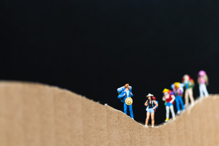 Miniature people :  Traveler with backpack walking on The paper mountain  . Travel and trekking Concept
