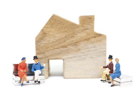 Miniature people :  Husband and wife sitting in front of house on white background  , Family concept.