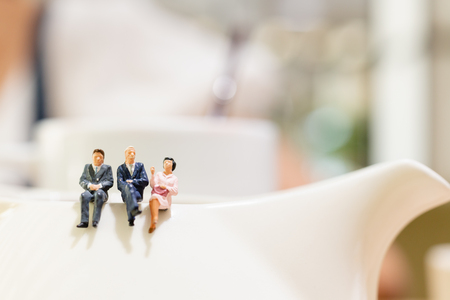 Miniature people : businessman and woman sitting on a cup of tea and copy space for text Banco de Imagens - 118408708