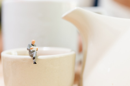 Miniature people : businessman and woman sitting on a cup of tea and copy space for text Stock Photo