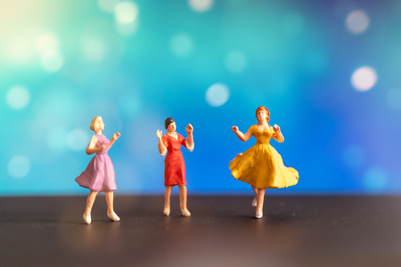 Miniature people , Woman in colored dress  dancing against bokeh background