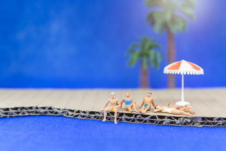 Miniature people wearing swimsuit relaxing on the beach with blue background Stock Photo
